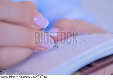 Woman Hand Holding Pen And Writing To Do List In Vintage Notebook Organizer - Close Up View. Motivat