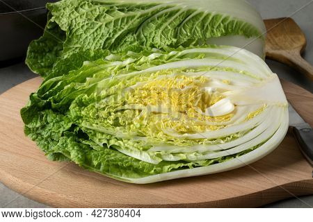 Whole and half fresh raw Chinese cabbage close up on a cutting board
