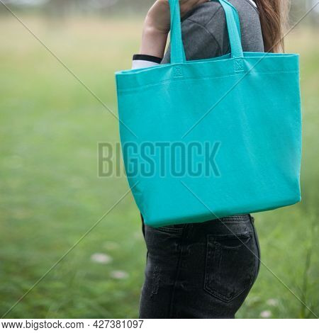 Woman holding emerald green tote bag, no face, outdoor