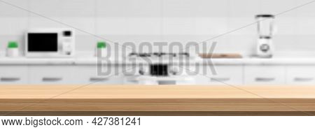 Wooden Counter Top On Kitchen Blur Background With Microwave Oven, Gas Stove, Blender And Cutting Bo