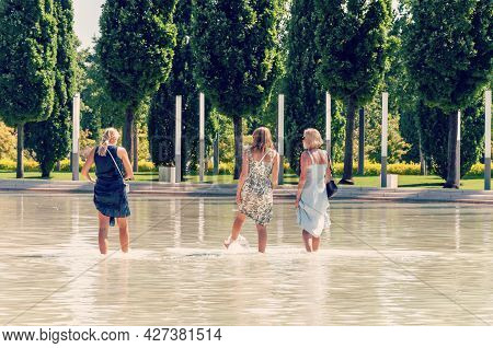 Krasnodar, Russia - July 16 2021: Three Women Standing In The Water In A Pond In A Park On A Hot, Su