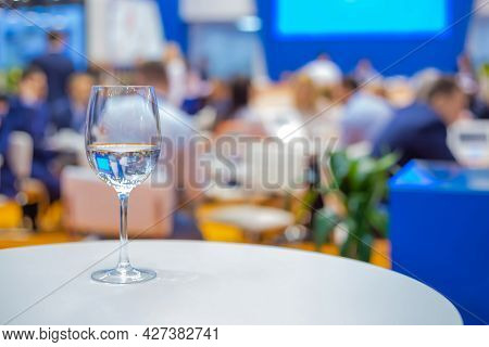 Close Up View: Glass Of Water, Champagne Or Wine On White Table Against Blurred Business Meeting, Co