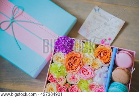 Close Up Top View Of Gift Box With Flowers And Colorful Macaroons At Flower Shop. Floristry, Handmad