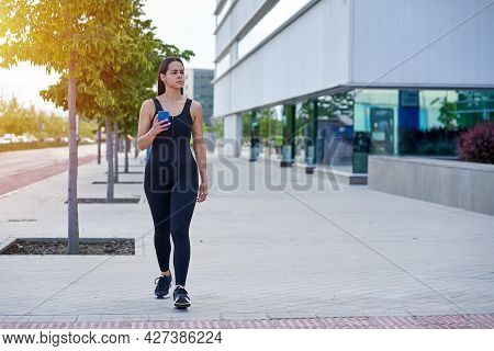 Female Model With Sportswear And Fit Body Walking With The Smartphone