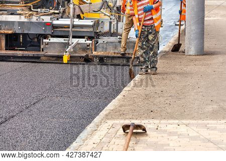 An Industrial Paver Is Laying A Layer Of New Hot Asphalt On The Carriageway. The Worker Controls The