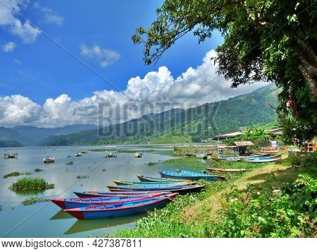 Row Of Colourful Boats On Calm Lake Pokhara, Nepal With Himalayas In Background