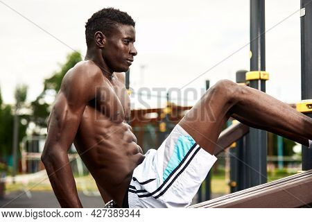 A Smiling African American Athlete Performs Abdominal Exercises, An Athlete In Excellent Physical Sh