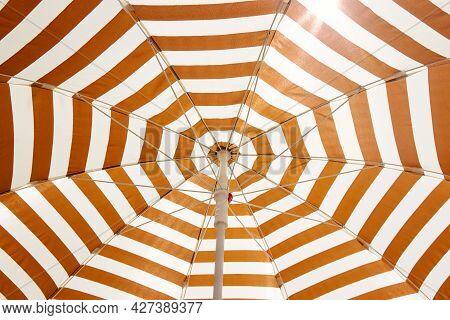 Striped Sun Umbrella Through Which The Sun's Rays Break Through. Concept Of Summer Hotel Holidays, B