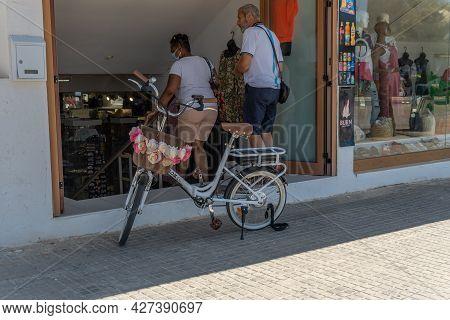 Platja De Palma, Spain; July 16 2021: Couple Of Tourists With Face Mask Entering A Souvenir Shop Dec