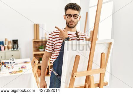 Arab young man at art studio pointing aside worried and nervous with forefinger, concerned and surprised expression