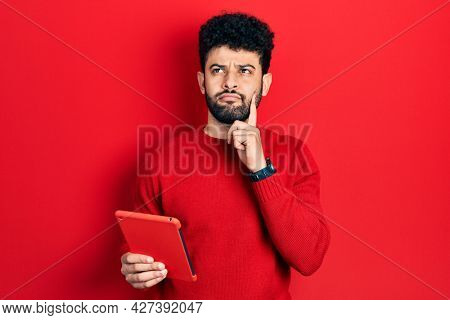 Young arab man with beard using touchpad device serious face thinking about question with hand on chin, thoughtful about confusing idea
