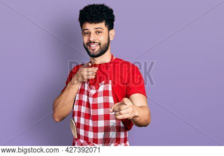 Young arab man with beard wearing cook apron pointing fingers to camera with happy and funny face. good energy and vibes.