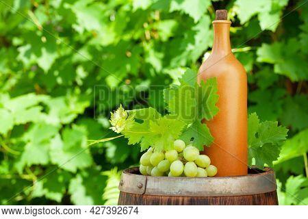 Wine bottle and grape vine on old wine barrel in front of vine leaves