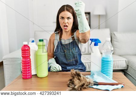 Young brunette woman wearing cleaner apron and gloves cleaning at home angry and mad raising fist frustrated and furious while shouting with anger. rage and aggressive concept.