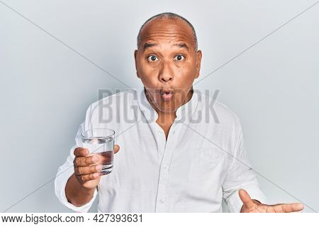 Middle age latin man drinking glass of water scared and amazed with open mouth for surprise, disbelief face