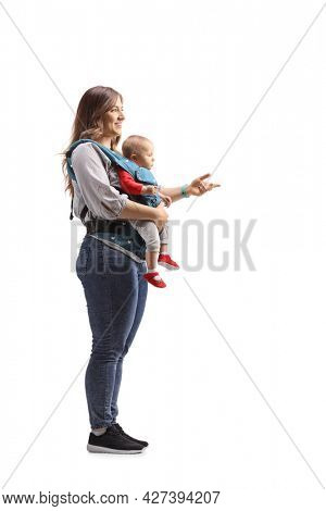 Full length profile shot of a mother standing with a baby in a carrier and gesturing with hand isolated on white background