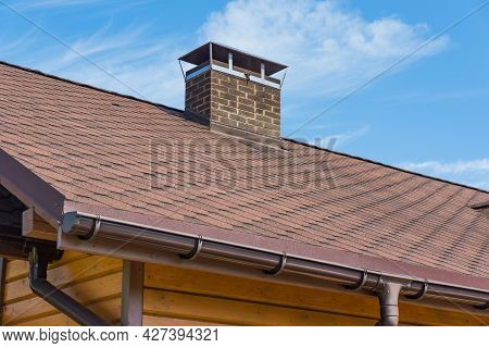 Bitumen Asphalt Roofing Shingles And Brick Chimney Pipe On A Wooden House. Individual Heating System