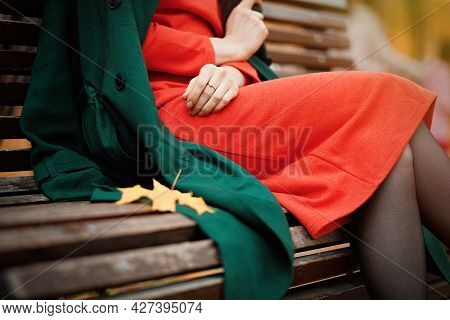 Woman In Orange Dress And Green Coat Sitting On Park Bench Outdoor. Autumn Fashion.
