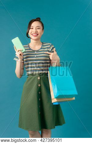 Beautiful Asian Woman Are Holding Shopping Bags And Mobile Phone With Face Happily In Blue Seamless