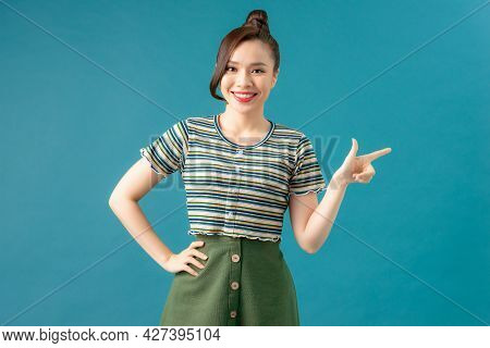 Young Asian Cute Woman Isolated On Blue Background Smiling Cheerfully Pointing With Forefinger Away.