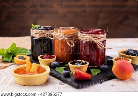 Delicious summer fruits jam - various berries and assorted jams on wooden table