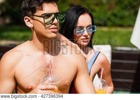 Shirtless Man Holding Orange Juice Near Blurred Girlfriend