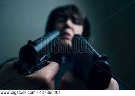 Close Up Of Two Guns Pointed At Mans Scarred Face. Interrogating A Guy In A Hood With Pistols. Threa