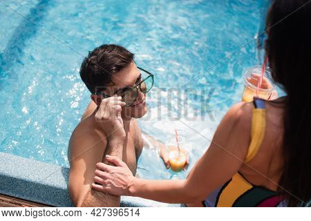 Overhead View Of Man Holding Sunglasses Near Blurred Girlfriend With Drink On Poolside