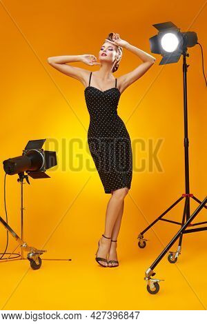 Beautiful glamorous woman in elegant evening dress posing in the light of flashes. Pin-up style in clothes, hair and make-up.