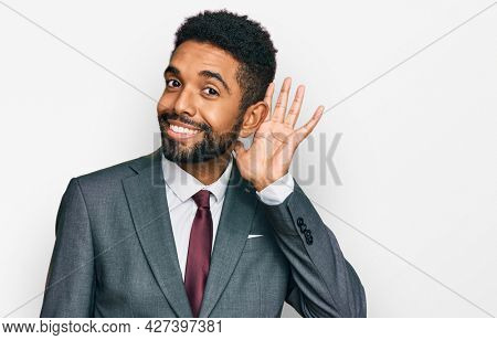 Young african american man wearing business clothes smiling with hand over ear listening an hearing to rumor or gossip. deafness concept.
