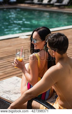 Shirtless Man Sitting Near Smiling Girlfriend With Orange Juice And Poolside