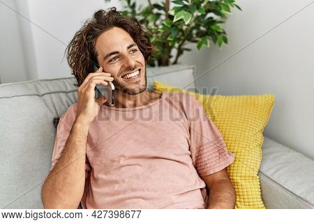 Young hispanic man smiling happy talking on the smartphone sitting on the sofa at home.