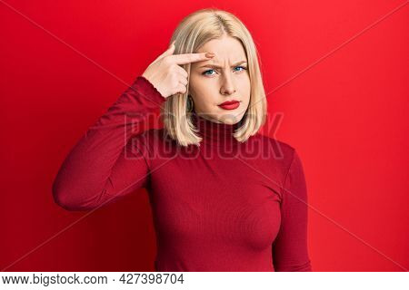 Young blonde woman wearing casual clothes pointing unhappy to pimple on forehead, ugly infection of blackhead. acne and skin problem