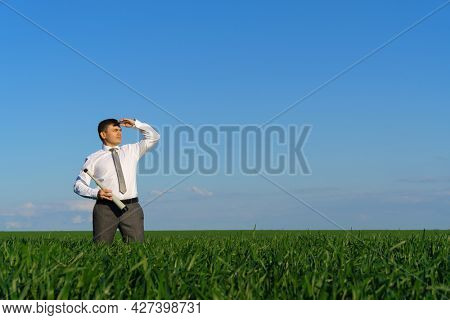 businessman poses with a spyglass, he looks into the distance and looks for something, green grass and blue sky as background