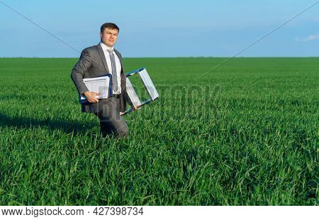 businessman poses in a green field, he goes with the documents and ladder, freelance and business concept, green grass and blue sky as background