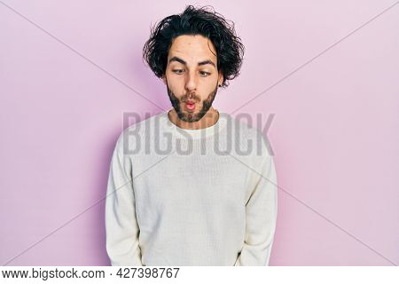 Handsome hispanic man wearing casual white sweater making fish face with lips, crazy and comical gesture. funny expression.