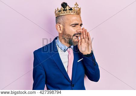 Young hispanic man wearing business clothes and king crown shouting and screaming loud to side with hand on mouth. communication concept.