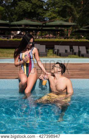 Cheerful Woman With Orange Juice Sitting On Poolside Near Boyfriend In Water