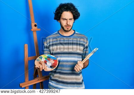 Handsome hispanic man standing drawing with palette by painter easel stand skeptic and nervous, frowning upset because of problem. negative person.