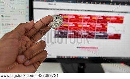 Close Up Of Hands Of Stock Trader Holding Ripple Xrp Cryptocurrency Token, Making Money With Initial