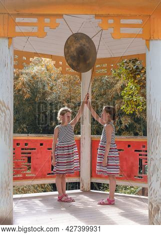 Two Tween Caucasian Girls Beating Gong In Classical Chinese Pavilion