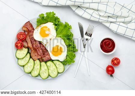 Fried Eggs With Bacon And Vegetables On A Gray Table, Food Background In Morning. Fresh Cucumbers An