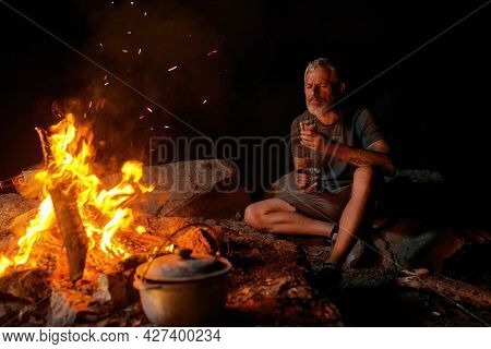 Hungry Man Eating Dinner While Sitting Near Campfire In The Wild. Outdoor Adventure, Tourism Concept