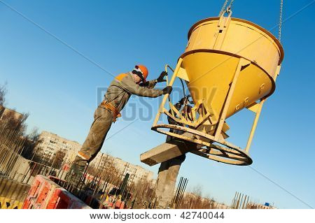 building workers at construction site doing concrete works with barrel