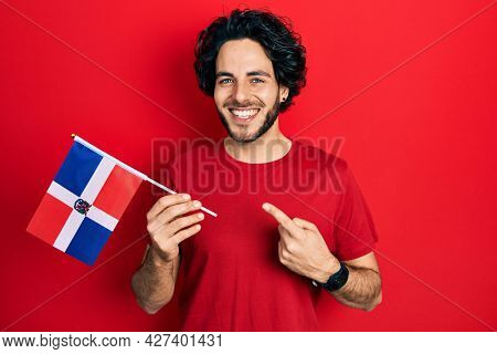 Handsome hispanic man holding dominican republic flag smiling happy pointing with hand and finger