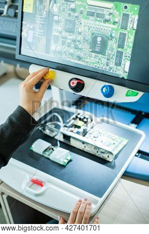 Woman Examines Microcircuits On A Special Apparatus For Reading The Visually Impaired.