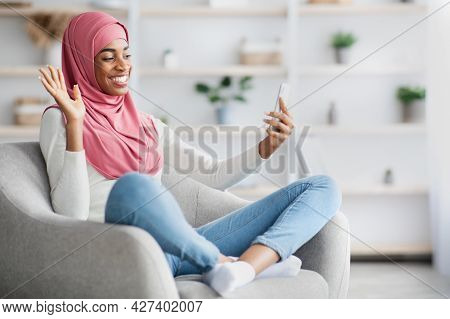 Black Muslim Lady In Hijab Making Video Call With Smartphone At Home