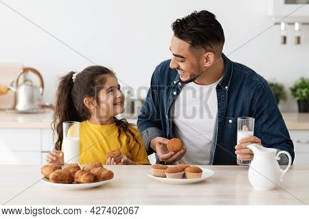 Little Arab Girl And Daddy Having A Bite In Kitchen At Home
