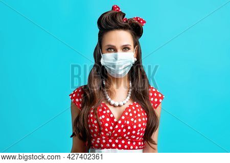 Young Pinup Lady In Retro Dress Wearing Mask Against Covid On Blue Background. Stay Safe, New Normal