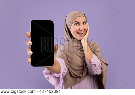 Mockup Image Of Smartphone With Black Blank Screen In Hands Of Happy Muslim Woman In Hijab Over Purp